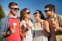 Group of smiling friends with ice cream outdoors. Friendship, leisure and people concept - group of smiling friends with ice cream outdoors in summer royalty free stock images
