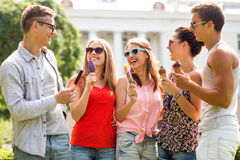 Group of smiling friends with ice cream outdoors Stock Photography