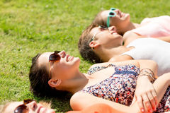 Group of smiling friends lying on grass outdoors Stock Image