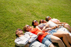 Group of smiling friends lying on grass outdoors Royalty Free Stock Images