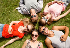 Group of smiling friends lying on grass outdoors Stock Images