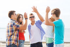 Group of smiling friends making high five outdoors Royalty Free Stock Images
