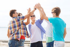 Group of smiling friends making high five outdoors Royalty Free Stock Photo