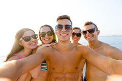 Group of smiling friends making selfie on beach. Friendship, leisure, summer, technology and people concept - group of smiling friends making selfie on beach stock image