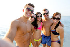Group of smiling friends making selfie on beach. Friendship, leisure, summer, technology and people concept - group of smiling friends making selfie on beach stock photo