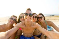 Group of smiling friends making selfie on beach Stock Photos