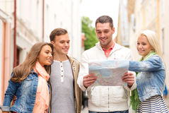 Group of smiling friends with map exploring city Stock Photos