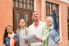 Group of smiling friends with map exploring city Stock Photo