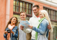 Group of smiling friends with map and photocamera Stock Images