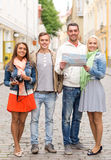 Group of smiling friends with map and photocamera Royalty Free Stock Images