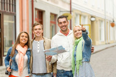 Group of smiling friends with map and photocamera Stock Photo