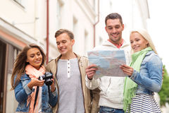 Group of smiling friends with map and photocamera Royalty Free Stock Image