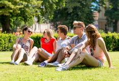 Group of smiling friends outdoors sitting on grass Royalty Free Stock Photography