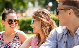 Group of smiling friends outdoors sitting in park Stock Image