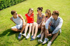 Group of smiling friends outdoors sitting in park Stock Photography