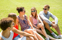 Group of smiling friends outdoors sitting in park Stock Images