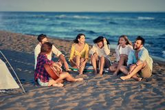 Smiling friends relaxing with playing guitar and sing a song on. Group of smiling friends relaxing with playing guitar and sing a song on sea beach royalty free stock images