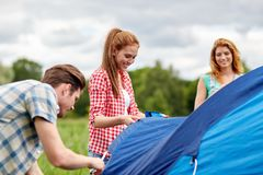 Group of smiling friends setting up tent outdoors Royalty Free Stock Photography