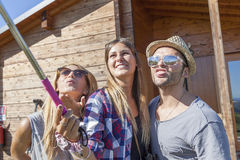 Group of smiling friends in single file taking funny selfie. With smart phone royalty free stock image
