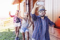Group of smiling friends in single file taking funny selfie. With smart phone royalty free stock photo