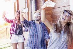 Group of smiling friends in single file taking funny selfie. With smart phone stock photos