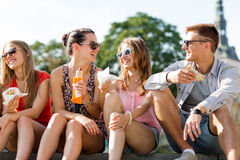 Group of smiling friends sitting on city square Stock Images