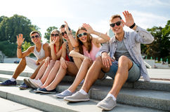 Group of smiling friends sitting on city street Royalty Free Stock Photos