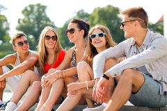 Group of smiling friends sitting on city street Stock Photo