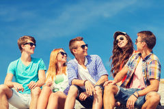 Group of smiling friends sitting on city street Royalty Free Stock Photo