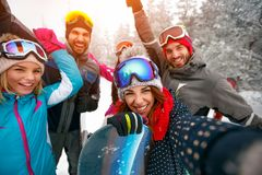 Group of smiling friends with ski on winter holidays - Skiers ha. Ving fun on the snow and making selfie Stock Photo