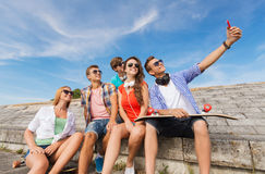 Group of smiling friends with smartphone outdoors Royalty Free Stock Photography