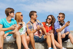Group of smiling friends with smartphones outdoors Stock Photography