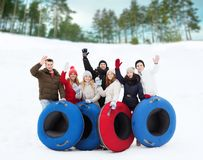 Group of smiling friends with snow tubes Stock Images