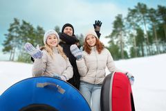 Group of smiling friends with snow tubes Stock Photography