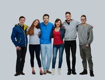 Group of smiling friends staying together and looking at camera isolated on white background. Stock Images