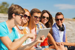 Group of smiling friends with tablet pc outdoors Stock Photo