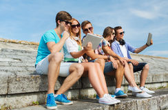 Group of smiling friends with tablet pc outdoors Stock Image