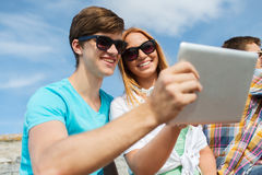 Group of smiling friends with tablet pc outdoors Royalty Free Stock Photo