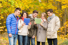 Group of smiling friends with tablets in park Stock Photo