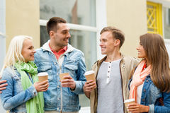 Group of smiling friends with take away coffee Royalty Free Stock Images