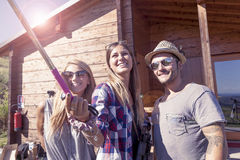 Group of smiling friends taking funny selfie with smart phone. On a vintage warm color filtered look stock photos