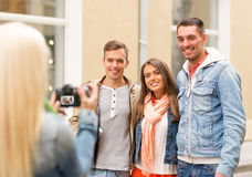 Group of smiling friends taking photo outdoors Royalty Free Stock Images