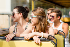 Group of smiling friends traveling by tour bus Stock Photos