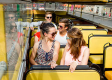 Group of smiling friends traveling by tour bus. Friendship, travel, vacation, summer and people concept - group of smiling friends traveling by tour bus Stock Photo