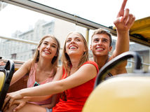 Group of smiling friends traveling by tour bus Stock Images