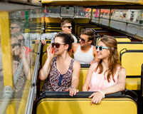 Group of smiling friends traveling by tour bus. Friendship, travel, vacation, summer and people concept - group of smiling friends traveling by tour bus Royalty Free Stock Images