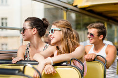 Group of smiling friends traveling by tour bus. Friendship, travel, vacation, summer and people concept - group of smiling friends traveling by tour bus Royalty Free Stock Image