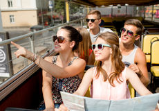 Group of smiling friends traveling by tour bus. Friendship, travel, vacation, summer and people concept - group of smiling friends with map traveling by tour bus Royalty Free Stock Images