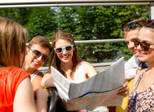 Group of smiling friends traveling by tour bus. Friendship, travel, vacation, summer and people concept - group of smiling friends with map traveling by tour bus Stock Photos