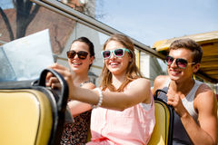 Group of smiling friends traveling by tour bus. Friendship, travel, vacation, summer and people concept - group of smiling friends with map traveling by tour bus Stock Photo